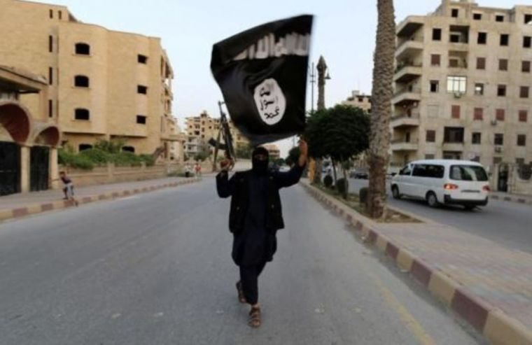 A member loyal to the Islamic State in Iraq and the Levant (ISIL) waves an ISIL flag in Raqqa, Syria in June 2014.