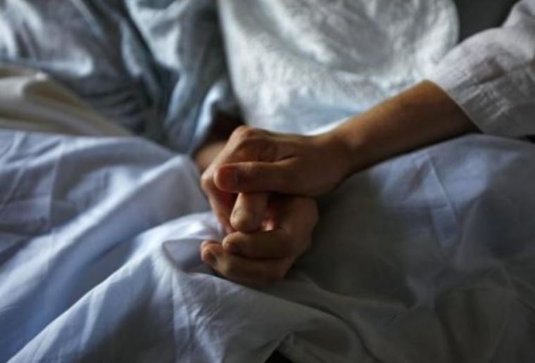 A photo of a woman holding the hand of her mother who is dying from cancer during her final hours at a palliative care hospital in Winnipeg.