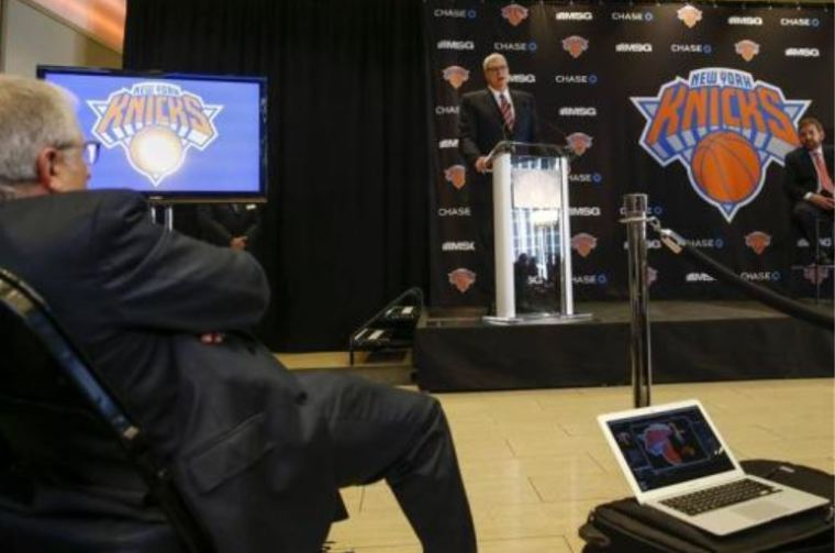 A photo of Phil Jackson speaking at a news conference announcing him as the team president of the New York Knicks basketball team.