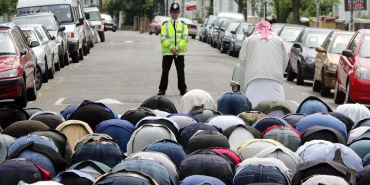 Police officer watches British Muslims