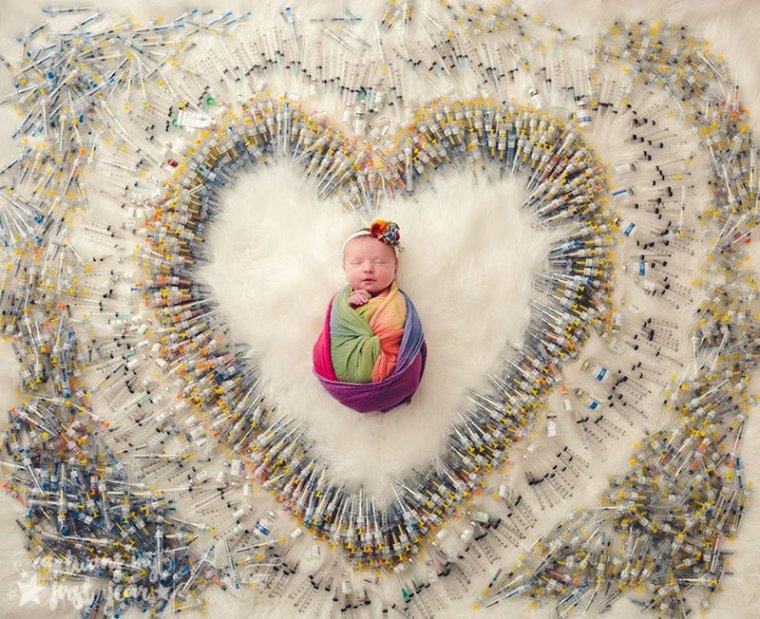 newborn baby surrounded by needles