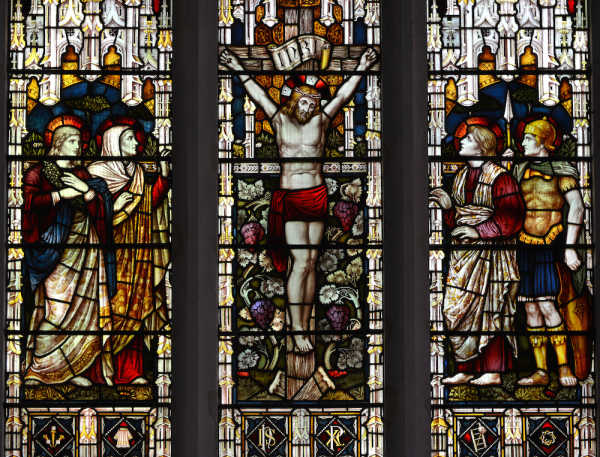 A Victorian (19th century) stained glass widow in an ancient English church, depicting the crucifixion of Jesus Christ.