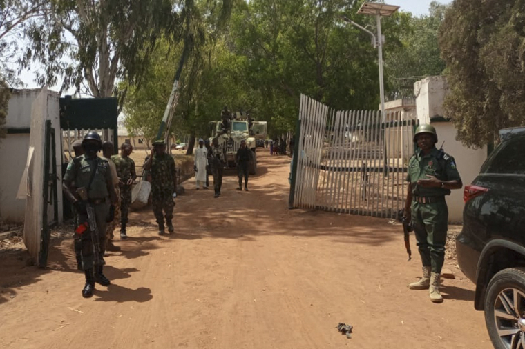 Nigerian soldiers and police officers stand at the entrance of the Federal College of Forestry Mechanisation in Mando, Kaduna state, on March 12, 2021, after a kidnap gang stormed the school shooting indiscriminately on March 11, 2021. | AFP via Getty Images/BOSAN YAKUSAK