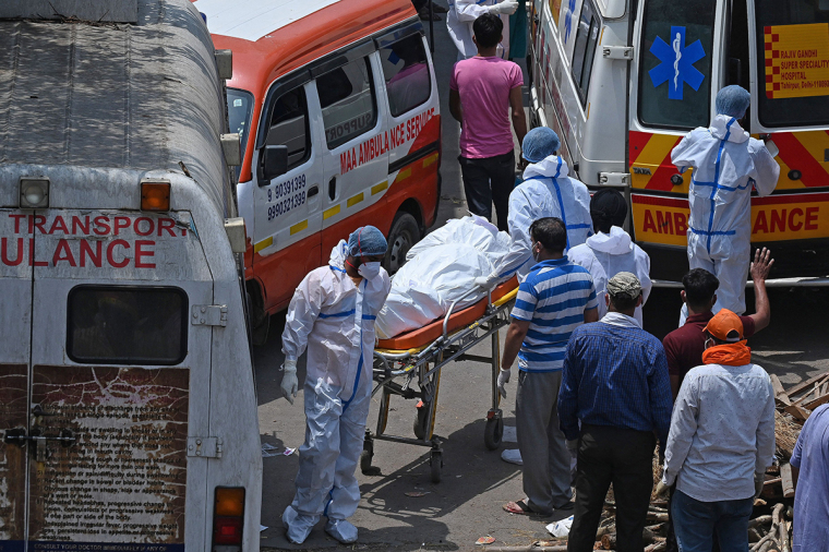 Family members and ambulance workers in PPE kits (Personal Protection Equipment) carry the bodies of victims who died of the COVID-19 coronavirus at a crematorium in New Delhi, India, on April 27, 2021. | PRAKASH SINGH/AFP via Getty Images