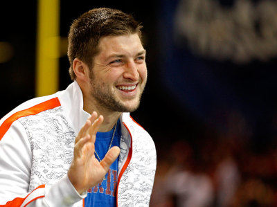 Former Florida Gators quarterback Tim Tebow waves as he stands on the sidelines before the Gators play against the Louisville Cardinals in the 2013 Allstate Sugar Bowl NCAA football game in New Orleans, Louisiana January 2, 2013.