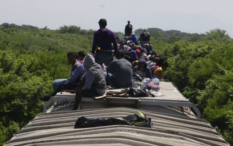 Unaccompanied minors ride atop the wagon of a freight train, known as La Bestia (The Beast) in Ixtepec, in the Mexican state of Oaxaca, June 18, 2014. | Reuters/Jose de Jesus Cortes